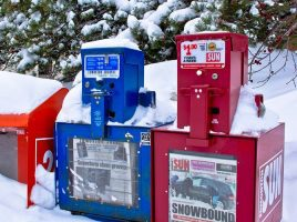 Snow-covered newspaper boxes in a small town in Alberta.